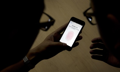 An Apple employee instructs a journalist on the use of the fingerprint scanner technology built into the company's iPhone 5S during a media event in Beijing, Sept. 11, 2013.