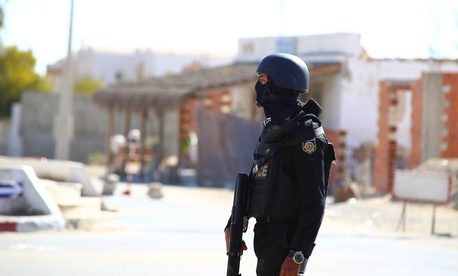 Tunisian police officers take positions as they search for attackers still at large in the outskirts of Ben Guerdane, southern Tunisia, Tuesday, Match 8, 2016.