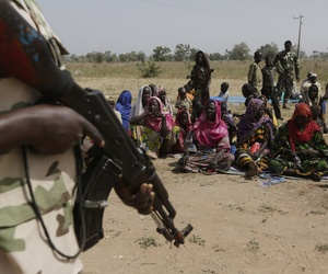 Nigerian soldiers guard people fleeing from Boko Haram's carnage and who about to be searched to ensure there are no insurgents infiltrating a refugee camp in Yola, Nigeria, Dec. 8, 2015.