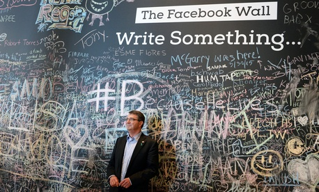 Defense Secretary Ash Carter stands in front of the Facebook wall during his visit to the company's headquarters in Menlo Park, Calif., April 23, 2015.