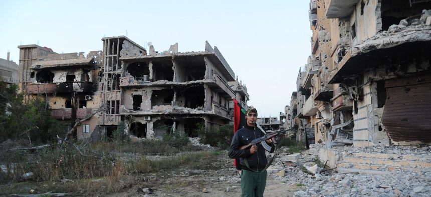 n this Feb. 23, 2016 file photo, a civilian fighter holding the Libyan flag stands in front of damaged buildings in Benghazi, Libya. The U.S., Europe and U.N. have all pinned their hopes for resolving Libya's chaos and blocking the Islamic State group's g