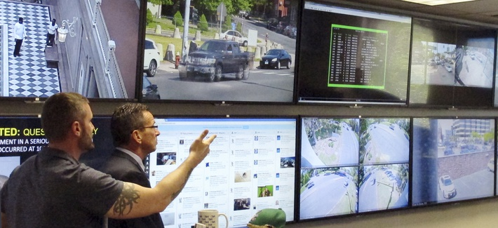 In this Friday, May 20, 2016 photo, Hartford police Sgt. Johnmichael O'Hare, left, shows Connecticut Gov. Dannel P. Malloy the police department's Real-Time Crime and Data Intelligence Center in Hartford, Conn.