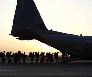 Marines and sailors with Marine Expeditionary Brigade in Afghanistan load onto a KC-130 aircraft on the Camp Bastion flightline, Oct. 27, 2014.