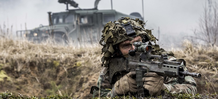 Latvian soldier looks down the barrel of his weapon with a Humvee for protection in the background, April 15, 2015.