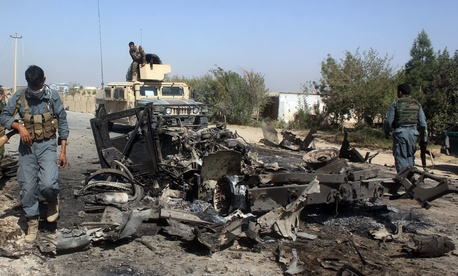 In this Oct. 2, 2015 file photo, Afghan security forces inspect the site of a U.S. airstrike in Kunduz city, north of Kabul, Afghanistan.
