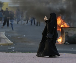A Bahraini woman photographs riot police during a clash with anti-government protesters in the western village of Shahrakan, on April 5, 2016.