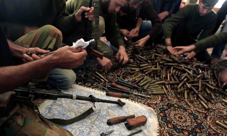 Free Syrian Army fighters clean their weapons and check ammunition at their base on the outskirts of Aleppo, Syria, Nov. 14, 2014.