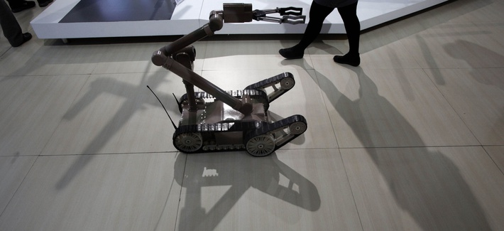A remote controlled robot cast a shadow at an exhibition on police equipment and anti-terror technologies held in Beijing, China, Thursday, May 19, 2011.