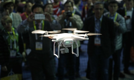 In this Jan. 7, 2016, file photo, a drone hovers at a booth during CES International, Thursday, Jan. 7, 2016, in Las Vegas.