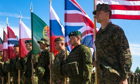 U.S. Marine Sgt. Steven Mashburn, a squad leader with Black Sea Rotational Force, right, holds the American flag during the opening ceremony for NATO's Exercise Saber Strike at the Pabrade Training Area, Lithuania, June 8, 2015.