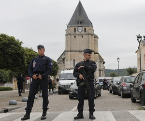 Police officers prevent the access to the church where an hostage taking left a priest dead the day before in Saint-Etienne-du-Rouvray, Normandy, France, Wednesday, July 27, 2016.