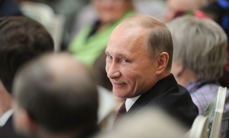Russian Prime Minister Vladimir Putin smiles as he attends a meeting with retirees in the Kremlin in Moscow, Thursday, Nov. 17, 2011.