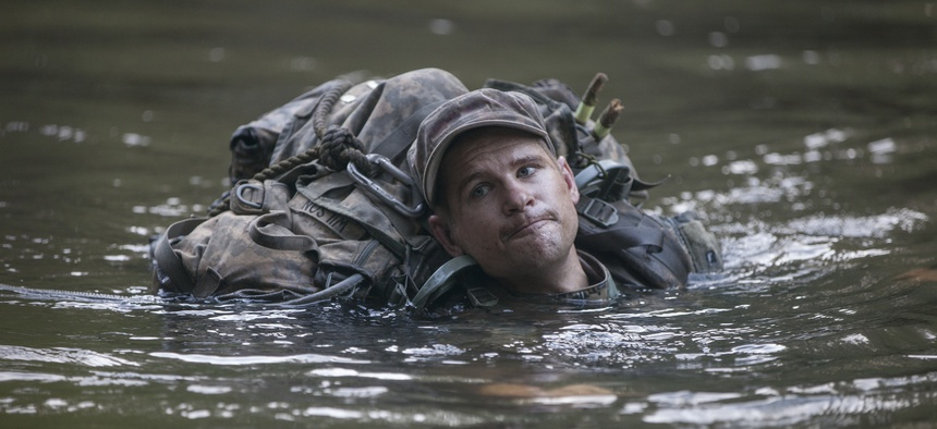 A U.S. Army Ranger student, assigned to the Airborne and Ranger Training Brigade, crosses a river using a single line rope bridge at Camp Rudder, Eglin Air Force Base, Fla., July 7, 2016.