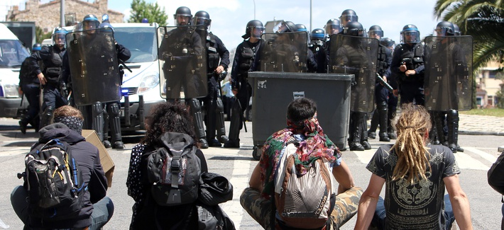 Protestors sit in front of riot police, after a demonstration in Marseille, southern France, Thursday, May 12, 2016.