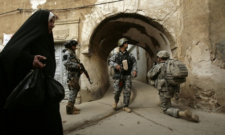 In this Thursday, April 23, 2009 file photo, an Iraqi woman passes U.S. troops and Iraqi police officers as they stand guard in the Bab al-Jadeed area of Mosul.