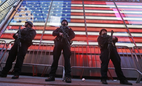 In this Nov. 14, 2015 file photo, heavily armed New York city police officers with the Strategic Response Group stand guard at the armed forces recruiting center in New York's Times Square.