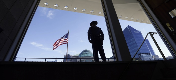 A State Capitol police officer stands watch from the Legislative Building during a Moral Monday rally outside the North Carolina Legislature in Raleigh, N.C., Monday, June 20, 2016.