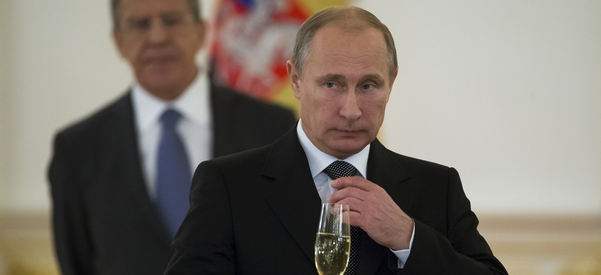 In a file photo from 2014, Russian President Vladimir Putin prepares to toast with ambassadors in the Grand Kremlin Palace in Moscow, Russia.