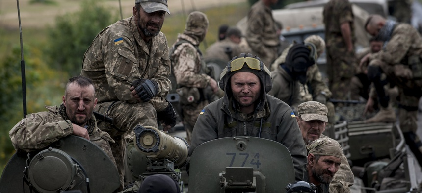 Russian-backed forces in eastern Ukraine are using rapidly innovating IT and EW tactics. Here, Ukrainian servicemen ride an armored vehicle near Krasnoarmiisk in eastern Ukraine in 2015.
