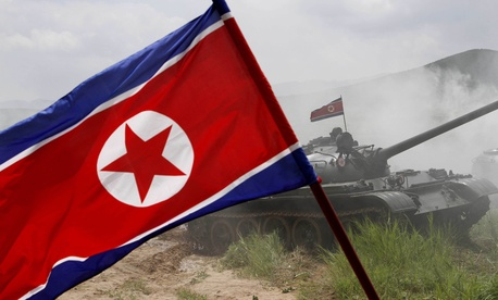 A North Korean flag flutters during a military exercise by the historic 105 tank unit at an undisclosed location in North Korea Friday, July 27, 2012.