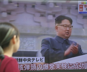A woman looks at a TV screen showing a file image of North Korean leader Kim Jong Un during a news program on the North's nuclear test, in Tokyo, Friday, Sept. 9, 2016.