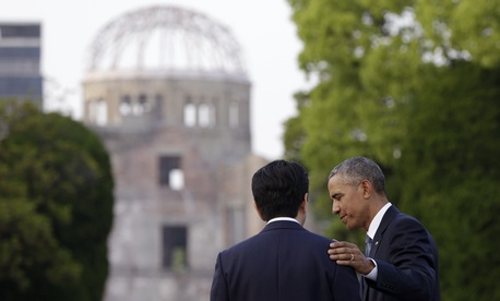 U.S. President Barack Obama, right, and Japanese Prime Minister Shinzo Abe speak with the Atomic Bomb Dome seen at rear at the Hiroshima Peace Memorial Park in Hiroshima, western Japan.