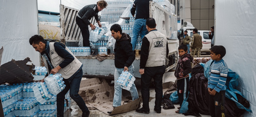 Men help unload a supply of mineral water for displaced civilians at a shelter in Makhmour, east of Mosul, Iraq, on March 28, 2016.