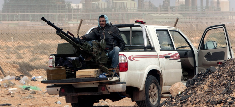An anti-government rebel sits with an anti-aircraft weapon in front an oil refinery in Ras Lanouf, eastern Libya, March 5, 2011.