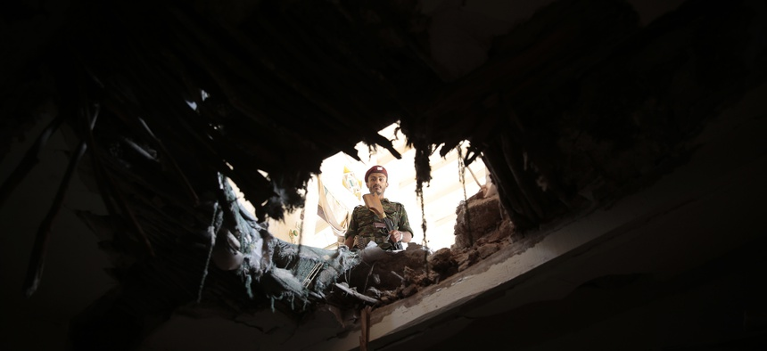 A soldier looks through a hole in a building damaged after an airstrike by Saudi-led coalition in Sanaa, Yemen, Tuesday, Sept. 20, 2016.