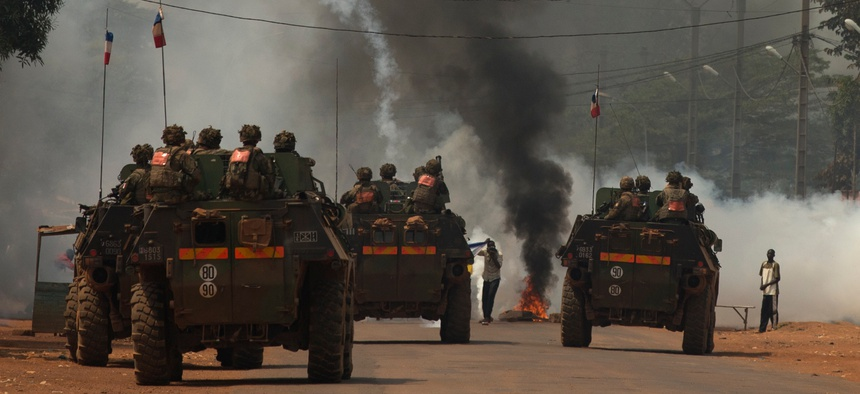 French soldiers fire tear gas as they attempt to contain a demonstration calling for the departure of French forces, in Bangui, Central African Republic, Dec. 22, 2013.