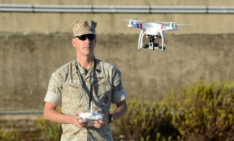 A U.S. Marine uses a commercial-grade Quadcopter to capture aerial video footage of the USNS William R. Button on the pier in Rota, Spain, during the preparation phase of Trident Juncture 2015.
