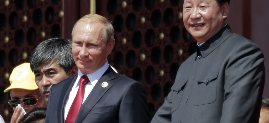 Chinese President Xi Jinping and Russian President Vladimir Putin observe a parade in Beijing, Sept. 3, 2015.