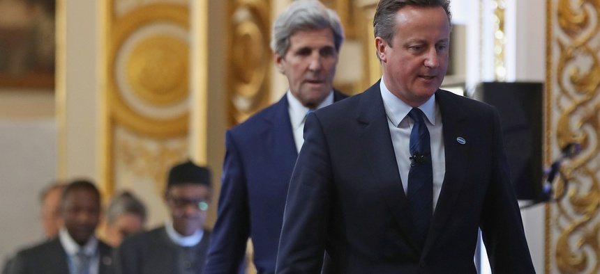 British Prime Minister Cameron, right, followed by U.S. Secretary of State John Kerry arrive to open London Anti-Corruption Summit on May 12, 2016, in London.