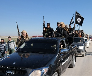 Islamic State militants pass by a convoy in Tel Abyad, northeast Syria, May 4, 2015.