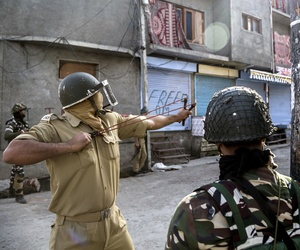 An Indian policeman uses a sling to shoot glass marbles at Kashmiri protesters during a protest in Srinagar, Indian controlled Kashmir, Friday, Oct. 7, 2016.