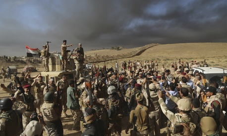 Iraqi army soldiers raise their weapons in celebration on the outskirts of Mosul, Iraq, Thursday, Oct. 20, 2016.