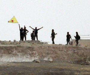 Kurdish fighters with the Kurdish People's Protection Units, or YPG, wave their yellow triangular flag in the outskirts of Tal Abyad, Syria, June 15, 2015.
