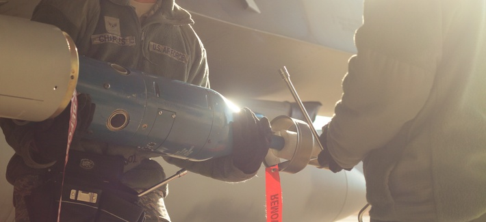 U.S. Airmen unload a GBU-12 Paveway II on an F-16C Fighting Falcon during day one of the annual load crew competition on Jan. 9 at Atlantic City Air National Guard Base, N.J.