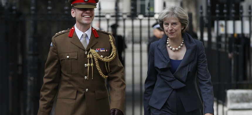 Britain's Prime Minister Theresa May walks with Col. John Clark a Military Advisor at 10 Downing Street in London, Sept. 22, 2016.