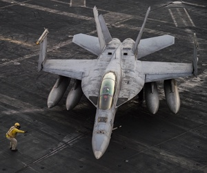 An F/A-18F Super Hornet deployed as part of Operation Inherent Resolve taxis across the flight deck the aircraft carrier USS Dwight D. Eisenhower.