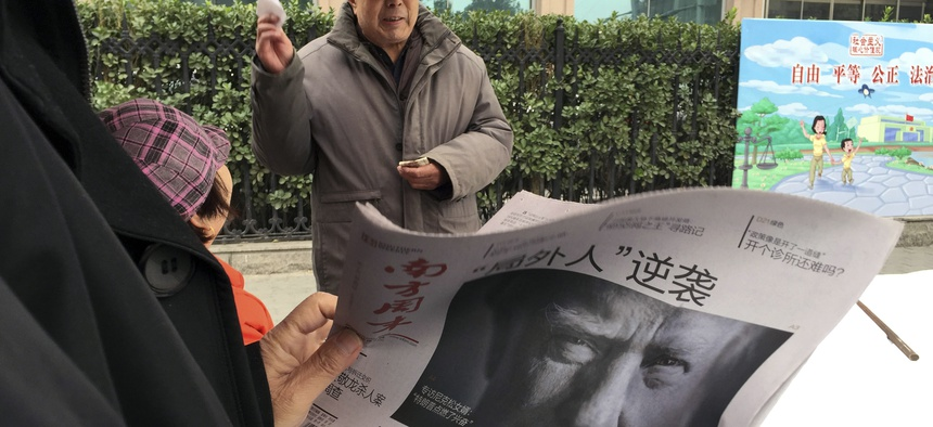 "In this Nov. 10, 2016 file photo, a Chinese man holds up a Chinese newspaper with the front page photo of U.S. President-elect Donald Trump and the headline ""Outsider counter attack"" at a newsstand in Beijing, China."