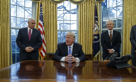 Vice President Mike Pence, left, and National Trade Council adviser Peter Navarro, right, wait for President Donald Trump to sign three executive orders, Monday, Jan. 23, 2017, in the Oval Office of the White House in Washington.