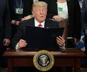 United States President Donald Trump (C) reads from one of the four executive orders he signed during a visit to the Department of Homeland Security January 25, 2017 in Washington, DC.