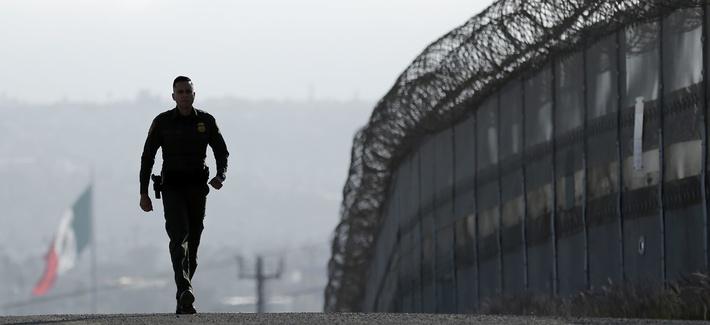 Border Patrol agent Eduardo Olmos walks near the secondary fence separating Tijuana, Mexico, background, and San Diego in San Diego, June 22, 2016.