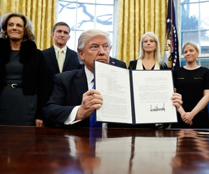 President Donald Trump holds up a signed National Security Presidential Memorandum in the Oval Office on Saturday.
