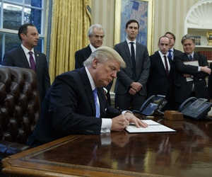 President Donald Trump signs an executive order implementing a federal government hiring freeze, Monday, Jan. 23, 2017, in the Oval Office of the White House in Washington.