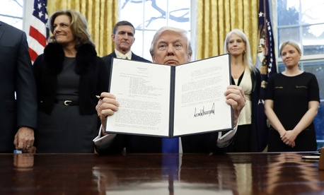 """President Donald Trump holds up another of his executive actions signed in his first two weeks, this one directing his administration to """"develop a comprehensive plan to defeat ISIS."""""""