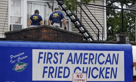 FBI agents walk around the roof outside an apartment during an investigation at a building, Sept. 19, 2016, in Elizabeth, N.J. FBI agents are searching the apartment that tied to Ahmad Khan Rahimi wanted for questioning in the New York City bombing.