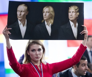 In this Dec. 23, 2016 file photo, a journalist holds a poster with portraits of Russian President Vladimir Putin, left, France's far-right National Front president, Marine Le Pen, center, and President-elect Donald Trump, prior to Putin's annual pr event.