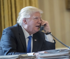 President Donald Trump speaks on the phone with Russian President Vladimir Putin, Saturday, Jan. 28, 2017, in the Oval Office at the White House in Washington.